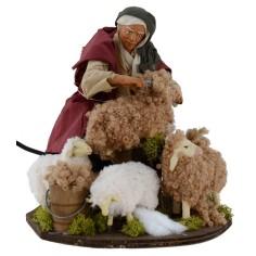 Pastore seduto che tosa le pecore in movimento serie 30 cm